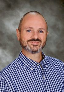 Terry Bacon smiling in a school photo with a gray background. He is wearing a blue and white checkered button-up shirt.
